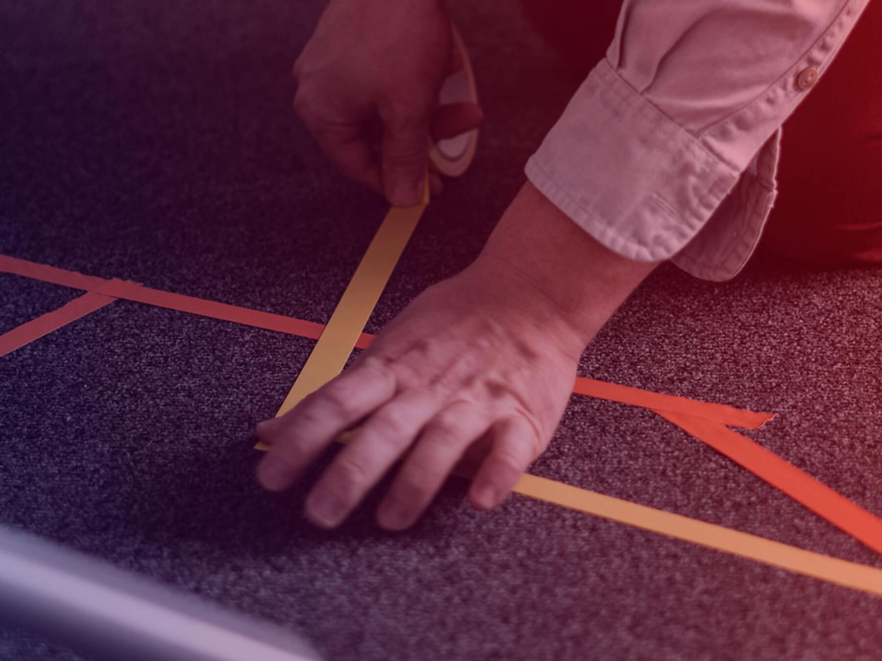 Bild einer Hand, die Streifen auf den Boden klebt